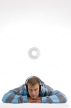 Laying young man with headphone stock photo, Laying young man with headphone on an isolated white background by Imagery Majestic