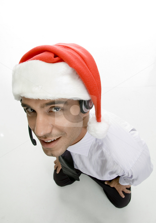 Businessman with headphone and santa cap stock photo, Businessman with headphone and santa cap with white background by Imagery Majestic