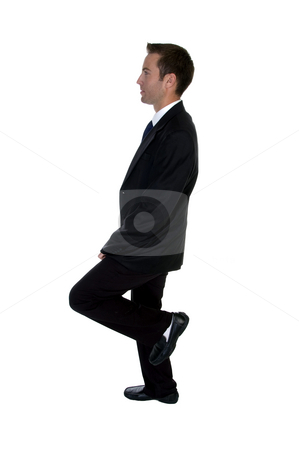 Young businessman benting one leg stock photo, Young businessman benting one leg against white background by Imagery Majestic