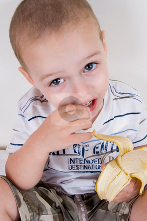 Cute boy holding peeled banana stock photo, Close up of cute boy holding peeled banana by Imagery Majestic