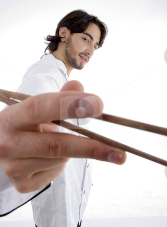 Young fellow in chef uniform holding chopsticks stock photo, Young fellow in chef uniform holding chopsticks on an isolated white background by Imagery Majestic