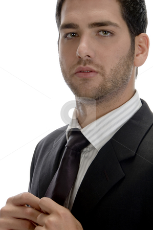 Businessman holding tie and looking to camera stock photo, Businessman holding tie and looking to camera on an isolated white background by Imagery Majestic