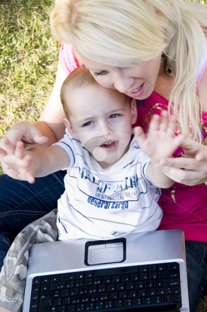 Caring mother with laptop and her child stock photo, Caring mother with laptop and her child sitting in her lap by Imagery Majestic