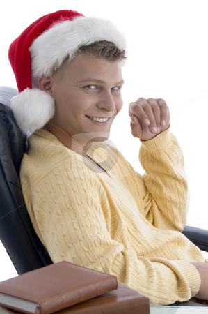 Handsome male wearing santa hat looking at camera stock photo, Handsome male wearing santa hat looking at camera with white background by Imagery Majestic