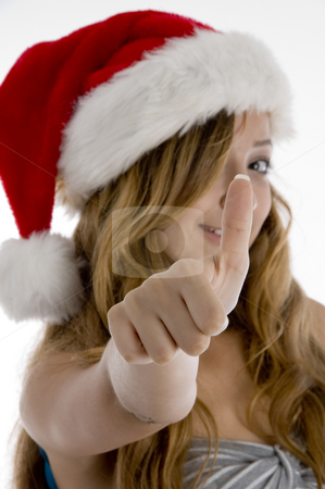 Girl showing her thumb stock photo, Girl with christmas hat showing her thumb on  an isolated white background by Imagery Majestic