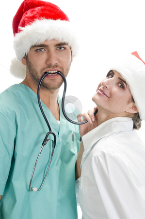Posing medical professionals with stethoscope and santa cap stock photo, Posing medical professionals with stethoscope and santa cap on an isolated white background by Imagery Majestic