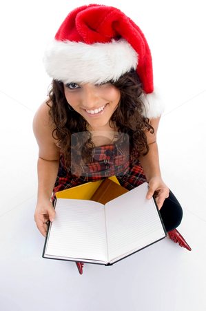 Smiling student with christmas hat and books stock photo, Smiling student with christmas hat and books on an isolated background by Imagery Majestic