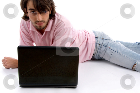 Laying man with laptop stock photo, Laying man with laptop on an isolated white background by Imagery Majestic