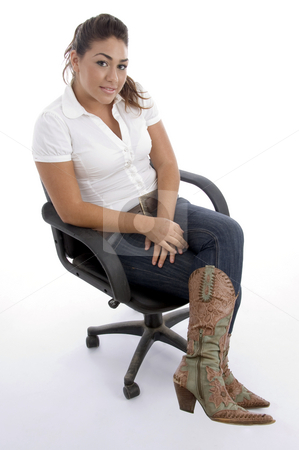Young pretty sitting on the chair and facing to camera stock photo, Young pretty sitting on the chair and facing to camera against white background by Imagery Majestic