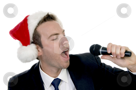 Young man singing into microphone with santa cap stock photo, Young man singing into microphone with santa cap on an isolated background by Imagery Majestic
