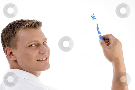 Adult caucasian holding toothbrush and posing to camera stock photo, Adult caucasian holding toothbrush and posing to camera with white background by Imagery Majestic