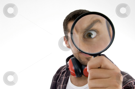 Man magnifing his eye  stock photo, Man magnifing his eye on an isolated white background by Imagery Majestic