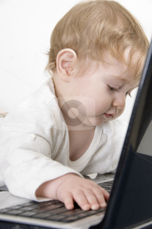 Curious baby playing with laptop stock photo, Curious baby playing with laptop by Imagery Majestic