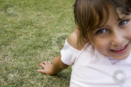 Smiling little girl sitting on grass stock photo, Close view of smiling little girl sitting on  grass by Imagery Majestic