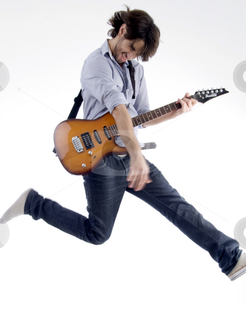 Smart fellow jumps while playing guitar stock photo, Man jumps while playing guitar on an isolated white background by Imagery Majestic