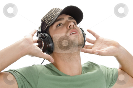 Young man with cap and headphone stock photo, Young man with cap and headphone on an isolated background by Imagery Majestic