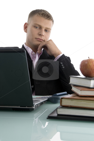 Young businessman looking into laptop stock photo, Young businessman looking into laptop with white background by Imagery Majestic