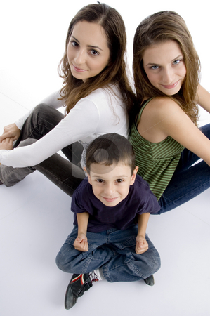 Young kid sitting with teenagers and facing at camera all stock photo, Young kid sitting with teenagers and facing at camera all, on an isolated white background by Imagery Majestic