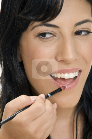 Smiling lady putting lipstick stock photo, Smiling lady putting lipstick by Imagery Majestic