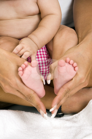 Mother holding her child's feet stock photo, Mother holding her child's feet on an isolated white background by Imagery Majestic