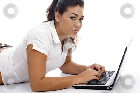 Young beautiful female working on laptop stock photo, Young beautiful female working on laptop on an isolated white background by Imagery Majestic