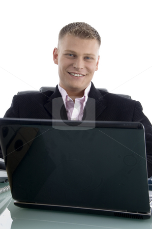 Smiling young businessman with laptop stock photo, Smiling young businessman with laptop against white background by Imagery Majestic