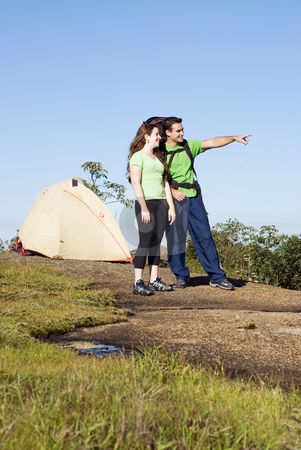 Couple Camping stock photo, Vertically framed shot of an attractive young couple camping by Orange Line Media