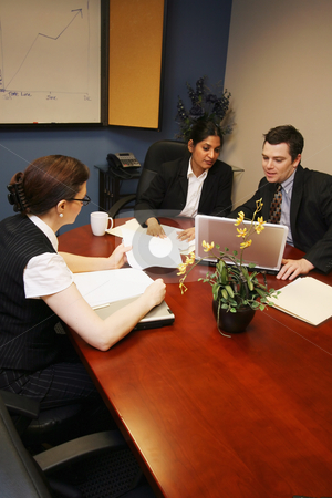 Business Meeting - Vertical stock photo, A vertical shot a businessman and two businesswomen looking at papers and laptops. by Orange Line Media