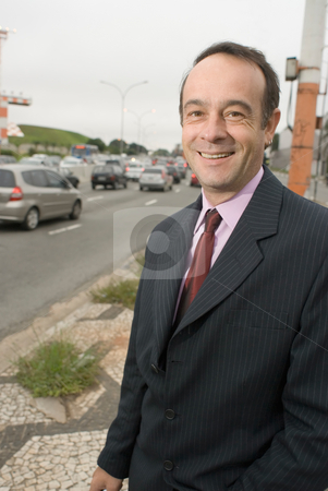 Businessman by the Roadside stock photo, A shot of a businessman standing by a road. by Orange Line Media