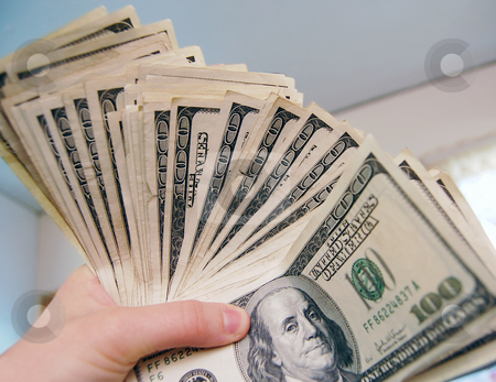 Hand Holding Money stock photo, A hand holding a lot of 100 dollar bills. by Crystal Srock