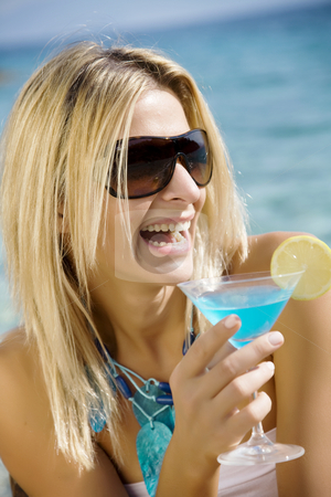 Cocktails by the sea stock photo, Laughing woman drinking cocktail by the sea by Liv Friis-Larsen