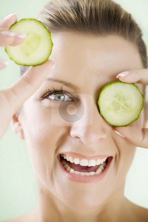 Fresh face stock photo, Smiling woman holding cucumber-slices in front of her eye by Liv Friis-Larsen