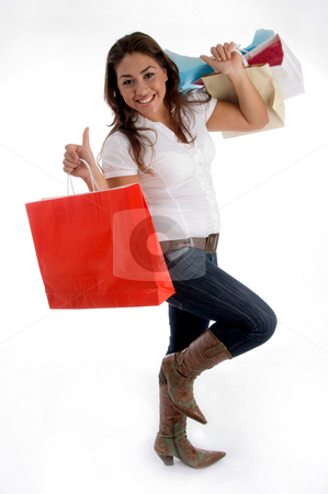 Happy girl holding shopping bags stock photo, Happy girl holding shopping bags on an isolated white background by Imagery Majestic