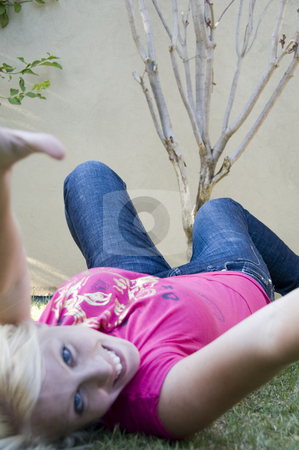 Happy beautiful woman lying in the garden stock photo, Happy beautiful woman lying in the garden and looking at the camera by Imagery Majestic
