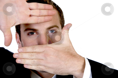 Young businessman making a finger frame in front of his eyes stock photo, Young businessman making a finger frame in front of his eyes with white background by Imagery Majestic