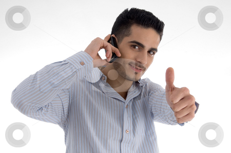 Man talking on cell phone and wishing goodluck stock photo, Man talking on cell phone and wishing goodluck on an isolated white background by Imagery Majestic