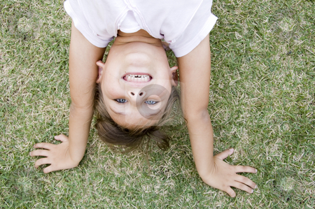 Girl doing cartwheel in the grass stock photo, Young girl doing cartwheel on the grass by Imagery Majestic