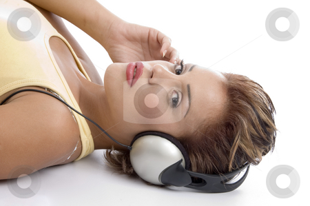 Laying woman with headphone looking at you stock photo, Laying woman with headphone looking at you on an isolated background by Imagery Majestic