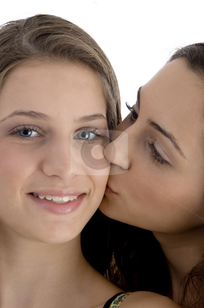 Female kissing her friend stock photo, Female kissing her friend on an isolated white background by Imagery Majestic