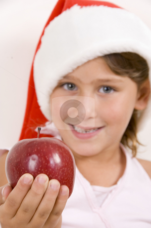 Girl wearing christmas hat and holding an apple stock photo, Girl wearing christmas hat and holding an apple in the palm of her hands by Imagery Majestic