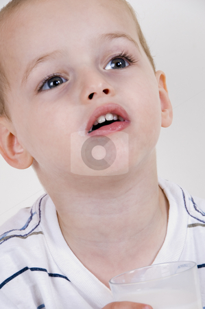 Cute little boy looking upward stock photo, Cute little boy looking upward and holding a glass of milk by Imagery Majestic