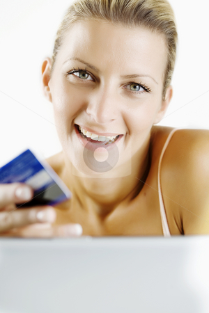 Shopping online stock photo, Young woman shopping through her laptop with credit card by Liv Friis-Larsen