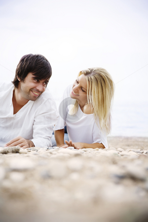 Couple on the beach stock photo, Happy couple talking in the sand by Liv Friis-Larsen