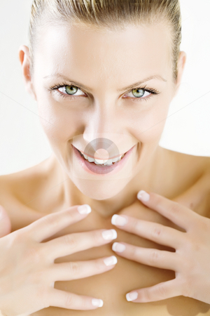 Body care stock photo, Portrait of smiling woman holding her hands in front of her body by Liv Friis-Larsen