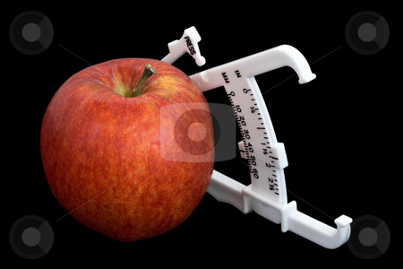 Apple and Calipers Over Black stock photo, An apple and bodyfat calipers isolated over a black background by Stephen Bonk