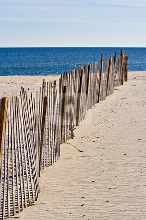 Fence on the Beach stock photo, An old wooden fence on the beach leading to the ocean by Stephen Bonk