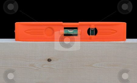Level stock photo, A red level on top of a wood 2X4 stud. The level indicates that the wood is level. by Stephen Bonk