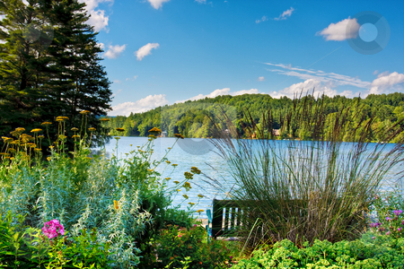 Scenic Lake stock photo, A scenic lake in the mountains. There is a bench and a flower garden in the foreground. by Stephen Bonk
