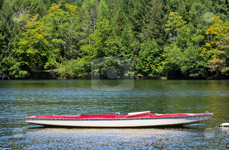 Sunfish boat on a lake stock photo, A docked sunfish boat without the sail on a lake. Green trees are in the background. by Stephen Bonk