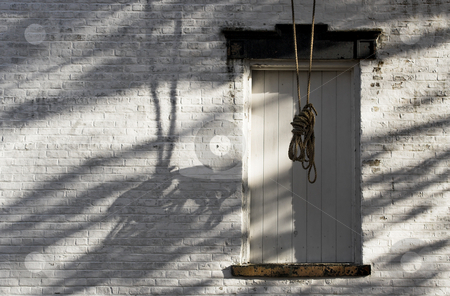 Rope and Shadows stock photo, An old building from a ghost town with a rope hanging from the top of the building. Evening side lighting causes the dramatic shadows. by Stephen Bonk